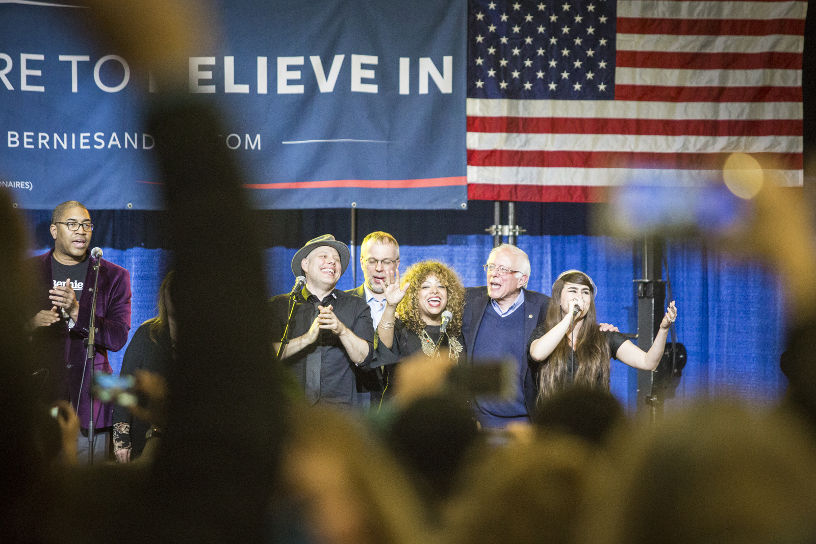 """Presidential hopeful Bernie Sanders sings """"This Land is My Land"""" onstage with local musicians at his primary rally in Essex, Vermont on Tuesday, March 1, 2016. by Monica Donovan for Heady Vermont"""