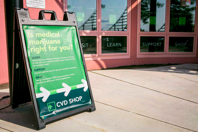 A sandwich board is prominently displayed outside the CVD Shop the Wing Building on the Bike Path in Burlington, Vermont on Wednesday, July 20, 2016. by Monica Donovan for Heady Vermont