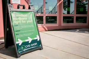 A CVD Shop sandwich board outside the Waterfront Wing Building along the Bike Path in Burlington, Vermont beckons the public to learn about medical marijuana on Wednesday, July 20, 2016. by Monica Donovan for Heady Vermont
